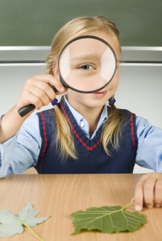 Little girl with magnifying glass in hand. Sitting at desk in front of blackboard. Magnifying her's eye. Looking at camera. Front view